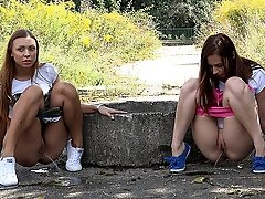 0  - Gorgeous girls both suffer pee desperation outside